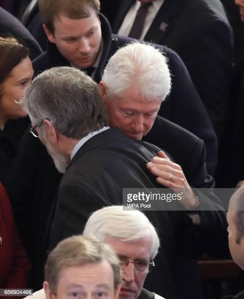 Former US President Bill Clinton hugs Sinn Fein president Gerry Adams after the funeral of Northern Ireland's former Deputy First Minister and exIRA...