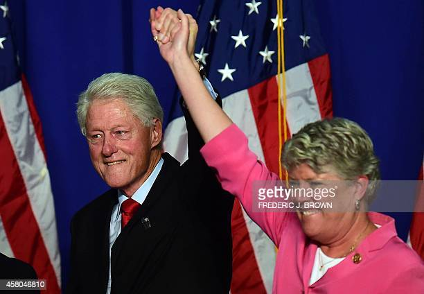 Former US President Bill Clinton lifts the arm of California Congresswoman Julia Brownley in a show of support during a Get Out The Vote rally in...