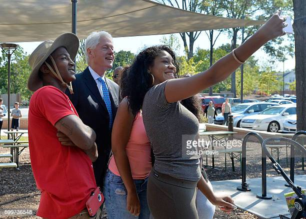 Former US President Bill Clinton poses for a photo with customers during a visit to the Durham CoOp before his campaign stop on September 6 2016 in...