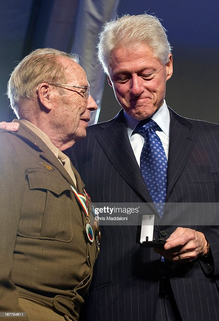 Former US President Bill Clinton presents World War II Army veteran Scottie Ooton, a member of the 84th Infantry Division which liberated Hannover-Ahlem concentration camp, the 20th anniversary pin of the United States Holocaust Memorial in Washington, D.C. on April 29, 2013.