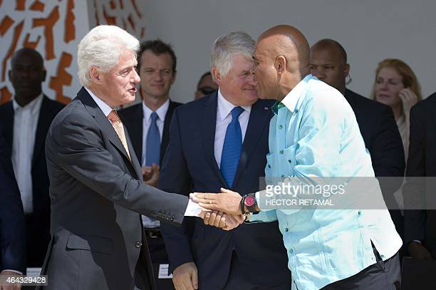 Former US President Bill Clinton shakes hands Haitian President Michel Martelly during the opening ceremony of the Marriott hotel in Port au Prince...