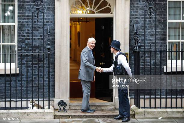 Former US President Bill Clinton shakes hands with a police officer as he arrives at Number 10 Downing Street on October 19 2017 in London England Mr...