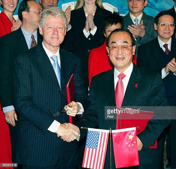 Former US President Bill Clinton shakes hands with Gao Qiang China's Executive Deputy Health Minister on February 23 in Beijing China The two signed...