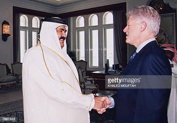 Former US president Bill Clinton shakes hands with Qatar's Emir Sheikh Hamad bin Khalifa alThani during their meeting in Doha 12 January 2004...