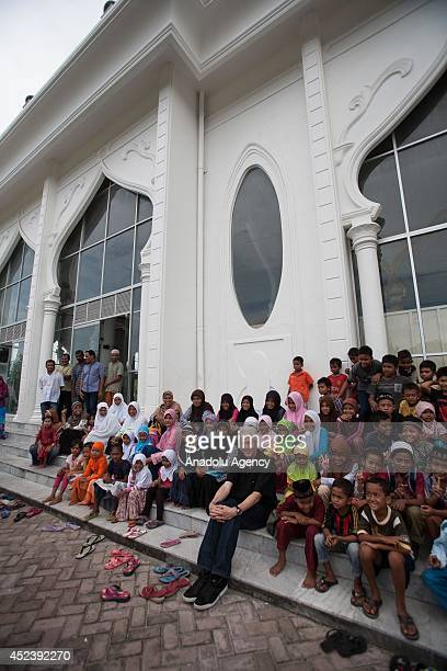 Former US president Bill Clinton sits with Acehnese children during a visit to the multilevel tsunami shelter site in Lampuuk in Banda Aceh in Aceh...
