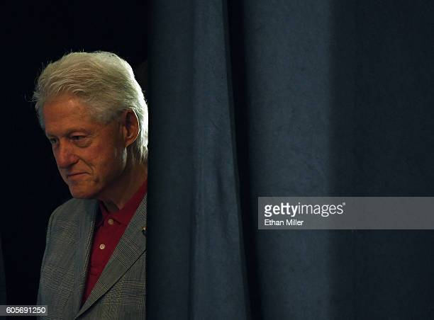 Former US President Bill Clinton stands behind a curtain backstage while waiting to speak at a campaign event for Democratic presidential nominee...