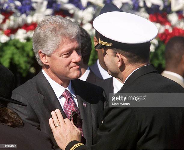 Former US President Bill Clinton talks to a member of the military during a Memorial Service at the Pentagon October 11 2001 in Arlington VA
