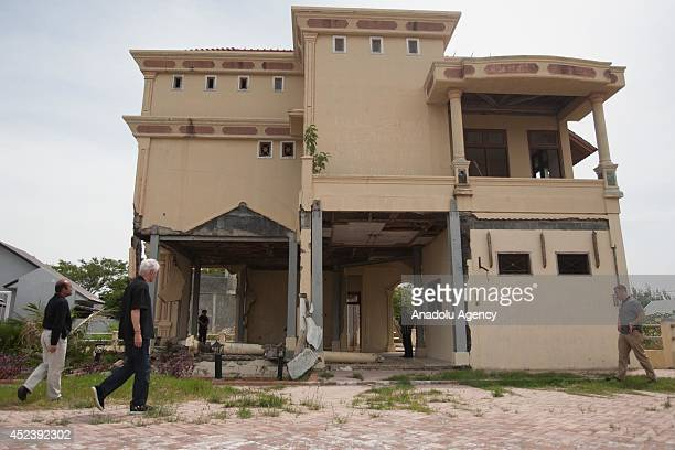 Former US president Bill Clinton views a building damaged by tsunami during a visit in Banda Aceh in Aceh province Indonesia on July 19 2014 Clinton...
