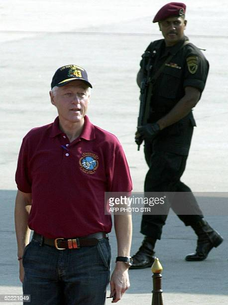 Former US president Bill Clinton walks after disembarking from a special US aircraft as a Sri Lankan commando covers from behind 20 February 2005 in...