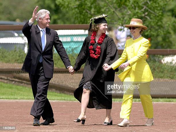 Former US President Bill Clinton waves as he walks hand in hand with daughter Chelsea center and his wife US Senator Hillary Clinton June 17 2001 in...