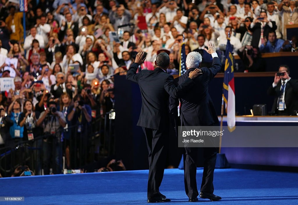Former U.S. President Bill Clinton waves with Democratic presidential candidate, U.S. President Barack Obama (L) on stage during day two of the Democratic National Convention at Time Warner Cable Arena on September 5, 2012 in Charlotte, North Carolina. The DNC that will run through September 7, will nominate U.S. President Barack Obama as the Democratic presidential candidate.
