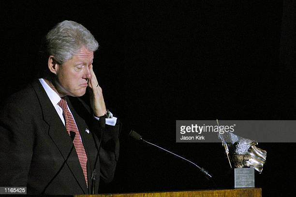 Former US President Bill Clinton wipes his eye during the 2001 Voter Improvement Programs Awards dinner sponsored by the AFLCIO October 1 2001 in...