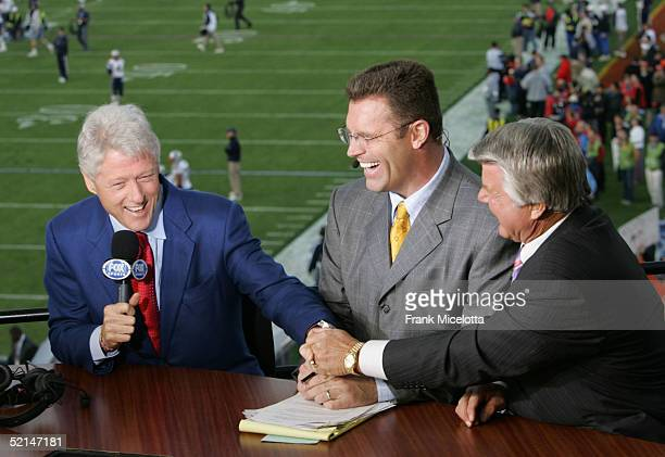 Former US President Bill Clinton with FOX sportscasters Howie Long and Jimmy Johnson speak at the FOX Broadcast booth during the XXXIX Superbowl...