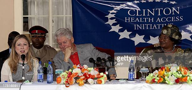 Former US President Bill Clinton's daughter Chelsea flanked by her father speaks during a joint press conference with Malawi's President Joyce Banda...