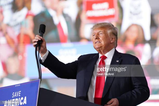Former US President Donald Trump adjusts the microphone at a rally on September 25, 2021 in Perry, Georgia. Republican Senate candidate Herschel...