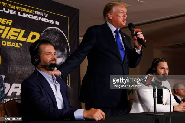 Former US President Donald Trump and Donald Trump Jr speak after the fight between Evander Holyfield and Vitor Belfort during Evander Holyfield vs....