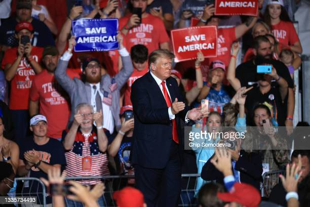 """Former U.S. President Donald Trump applauds as he finishing addressing a """"Save America"""" rally at York Family Farms on August 21, 2021 in Cullman,..."""