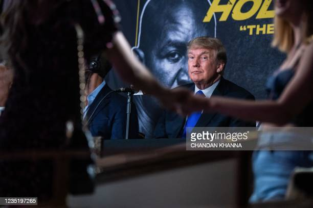 Former US President Donald Trump watches women dance as he hosts the Holyfield vs Belford boxing match live with commentary at Hard Rock Live in...
