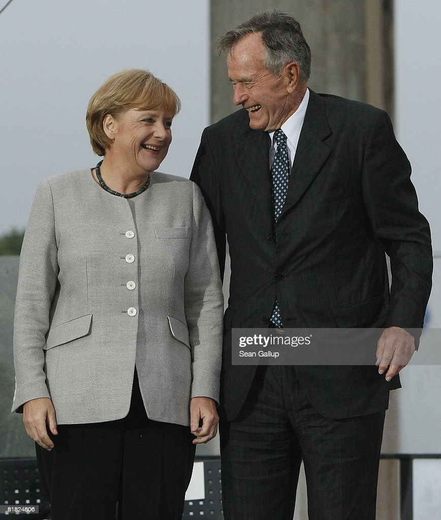 Former U.S. President George Bush and German Chancellor Angela Merkel chat after speaking at the official opening of the new U.S. embassy on July 4, 2008 in Berlin, Germany. Architectural critics claim the embassy, designed by American architect Moore Ruble Yudell, offers little in architectural innovation or design.