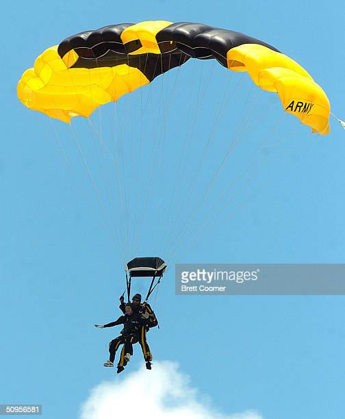 Former US President George Bush harnessed to US Army Golden Knight Sgt Bryan Schnell glides to earth as he makes a tandem parachute jump to celebrate...