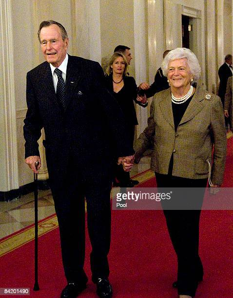 Former US President George H W Bush and former First Lady Barbara Bush arrive to the East Room of the White House for the reception in honor of the...