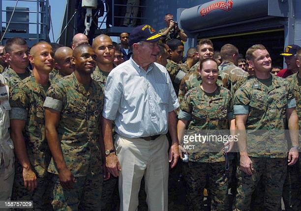 Former US President George H W Bush is flanked by US Marine Corps Marines while posing for a photo aboard the US Navy Whidbey Island Class Amphibious...