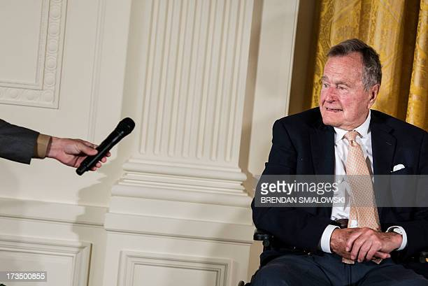 Former US President George H W Bush is handed a microphone during an event in the East Room of the White House on July 15 2013 in Washington...