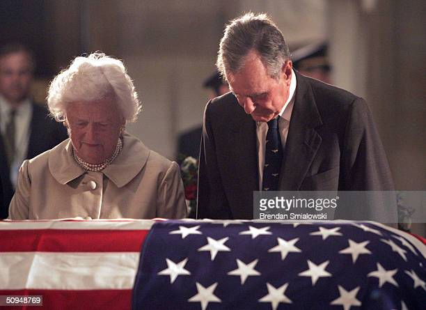 Former US President George HW Bush and his wife Barbara Bush pay their respects to former US President Ronald Reagan in the US Capitol Rotunda June...