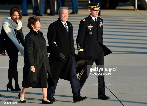 Former US President George W Bush and former First Lady Laura Bush walk from Special Air Mission 41 the plane that carried his father former US...