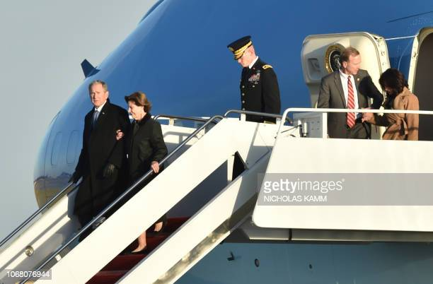 Former US President George W Bush and former first lady Laura Bush arrive at Joint Base Andrews Maryland on December 3 accompanying the flagdraped...