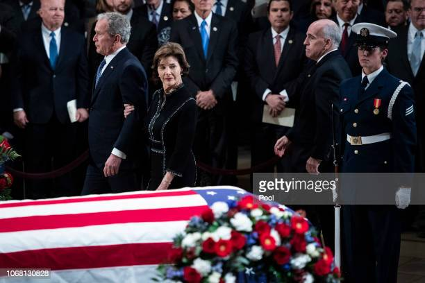 Former US President George W Bush and former first lady Laura Bush look back at the casket containing the remains of former US President George HW...