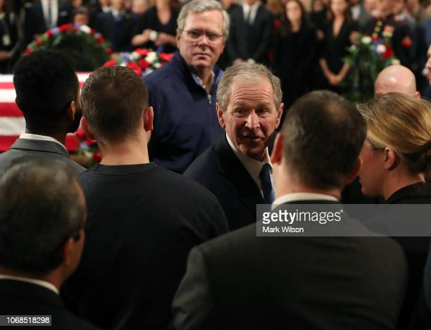 Former U.S. President George W. Bush and his brother Jeb Bush greet mourners in front of the casket of the late former President George H.W. Bush as...