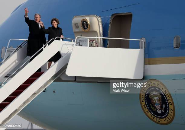 Former US President George W Bush and his wife Laura Bush wave after the casket of former US President George HW Bush was loaded onto a US Air Force...