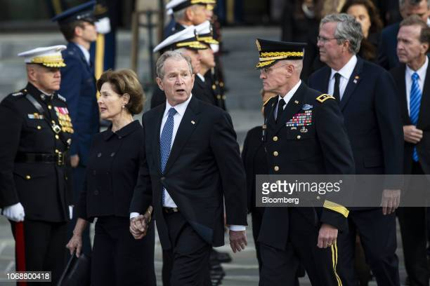 Former U.S. President George W. Bush, center, speaks with a member of the military while departing with former U.S. First Lady Laura Bush, and Jeb...
