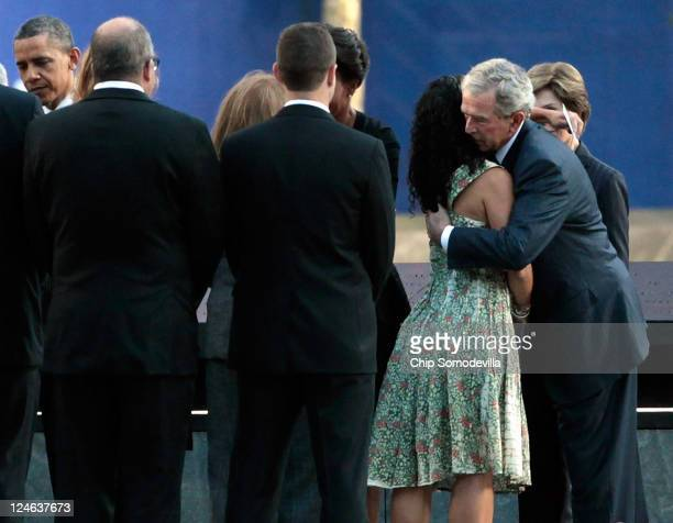 Former US President George W Bush embraces victims' family members at the 9/11 Memorial during the tenth anniversary ceremonies of the September 11...