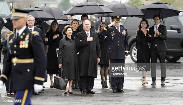 Former U.S. President George W. Bush, from center left, former U.S. First Lady Laura Bush, and Jeb Bush, former governor of Florida, stand as joint...