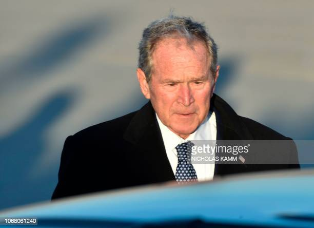 Former US President George W Bush gets into car after walking from Special Air Mission 41 the plane that carried his father former US President...
