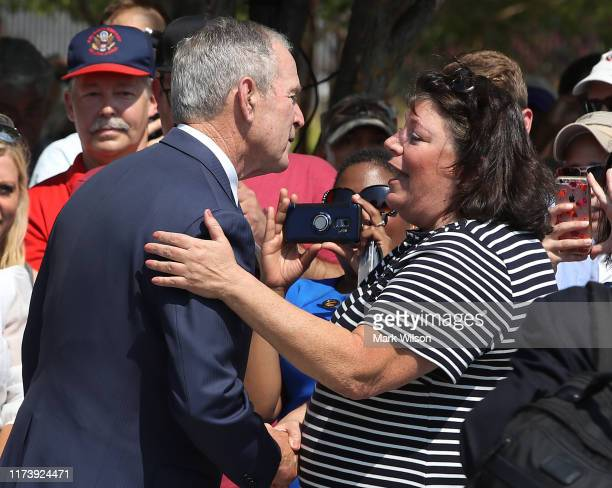 Former US President George W Bush greets Lisa Dolan whose husband US Navy Capt Robert Dolan was killed at the Pentagon during a wreathlaying ceremony...