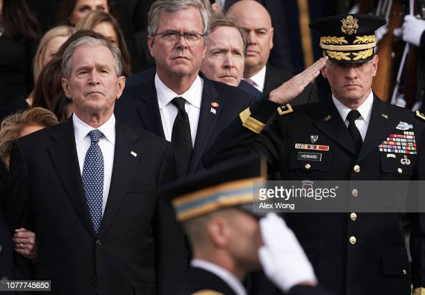Former US President George W Bush his brothers Jeb Bush and Neil Bush watch a joint service honor guard carry the casket of their father and former...