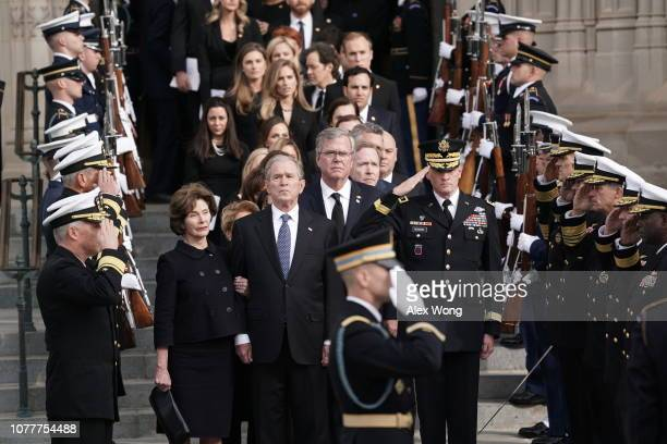 Former US President George W Bush his wife Laura Bush and his brothers Jeb Bush and Neil Bush watch a joint service honor guard carry the casket of...