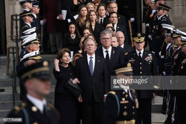 Former US President George W Bush his wife Laura Bush his brothers Jeb Bush and Neil Bush and other members of the Bush family watch a joint service...