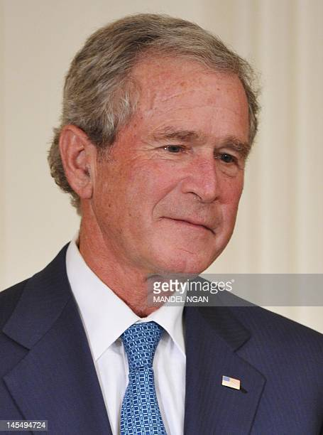 Former US President George W Bush is seen on stage for the unveiling of he and his wife's portraits May 31 2012 in the East Room of the White House...