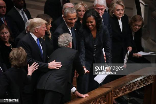 Former US President George W Bush leans across President Donald Trump and first lady Melania Trump to greet fellow former presidents Barack Obama...