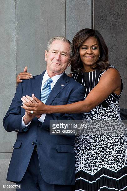 Former US President George W Bush receives a hug from US First Lady Michelle Obama as they attend the opening ceremony for the Smithsonian National...