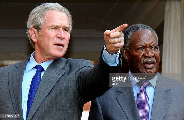 Former US President George W Bush talks to Zambian President Michael Sata on July 4 2012 at the State house in Lusaka Bush is in Zambia as part of a...