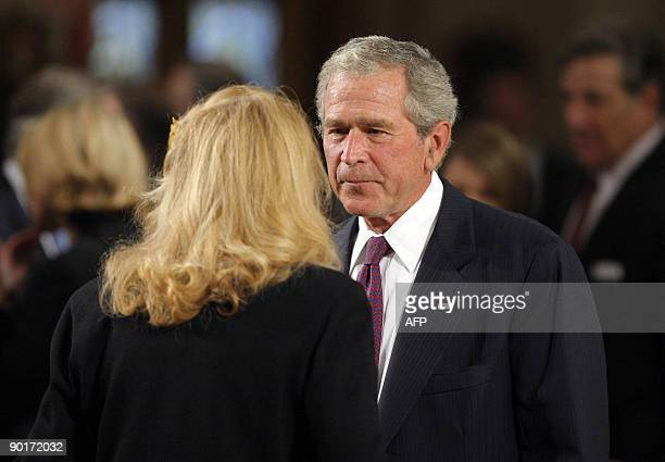 Former US President George W Bush talks with US Senator Edward Kennedy's exwife Joan Kennedy as they await the start of the funeral services for US...