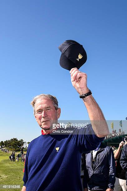 Former US President George W Bush tips his cap to fans on the first hole tee box during the second round of The Presidents Cup at Jack Nicklaus Golf...