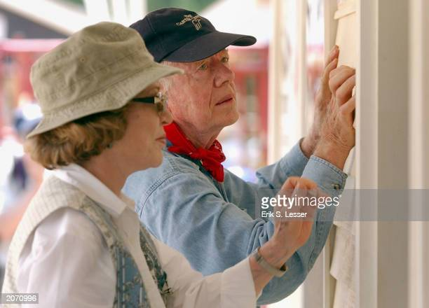 Former US President Jimmy Carter and his wife Rosalyn attach siding to the front of a Habitat for Humanity home being built June 10 2003 in LaGrange...