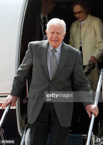 Former US president Jimmy Carter and his wife Rosalynn get down the plane upon their arrival at Queen Alia international airport in Amman on April 20...