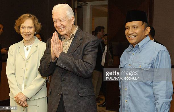 Former US president Jimmy Carter gestures to the press after his meeting with Indonesian presidential candidate Amien Rais in Jakarta 04 July 2004 as...